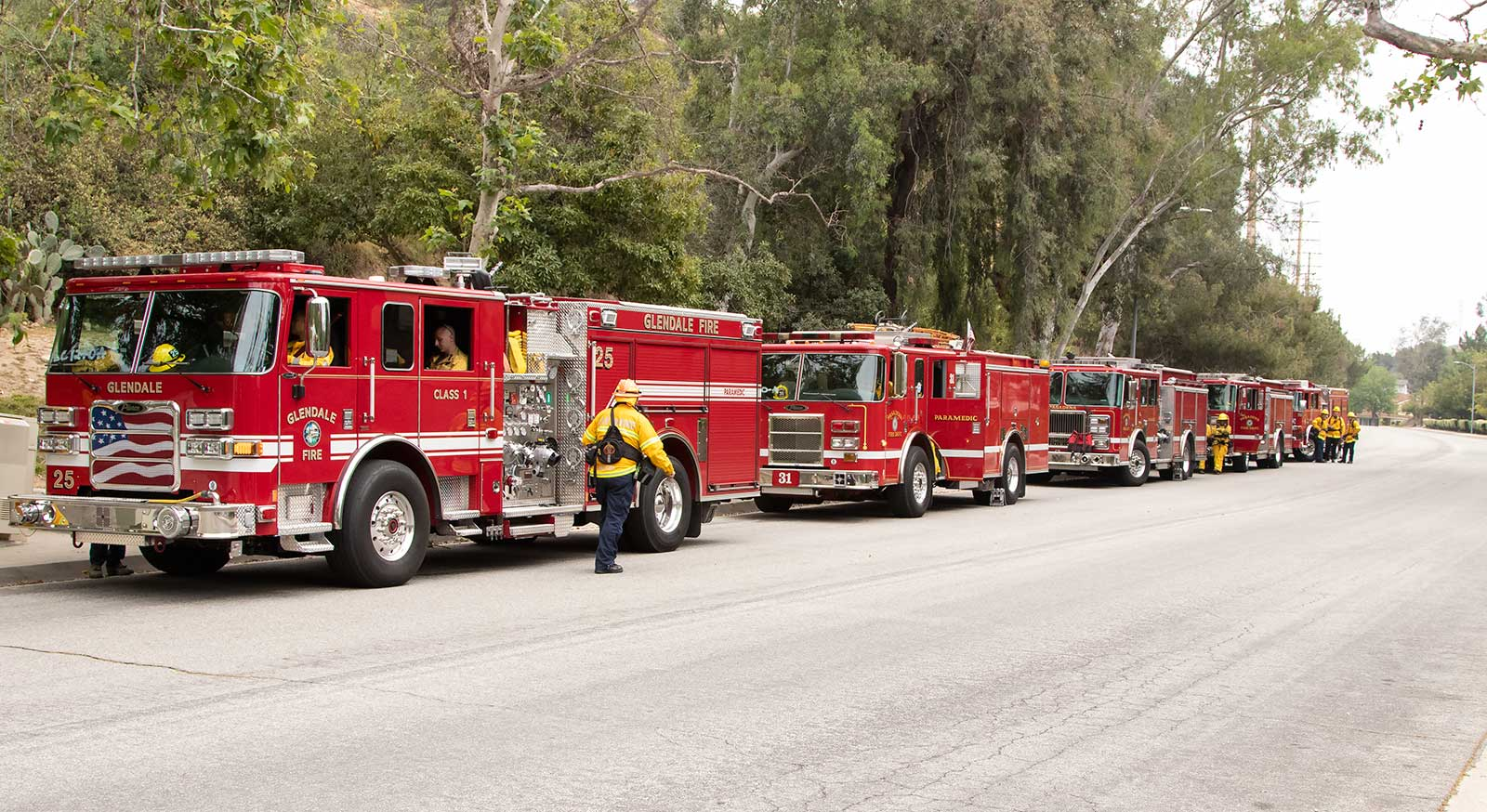Firetrucks ligned up to take part in a wildfire drill. Firefighters gather.