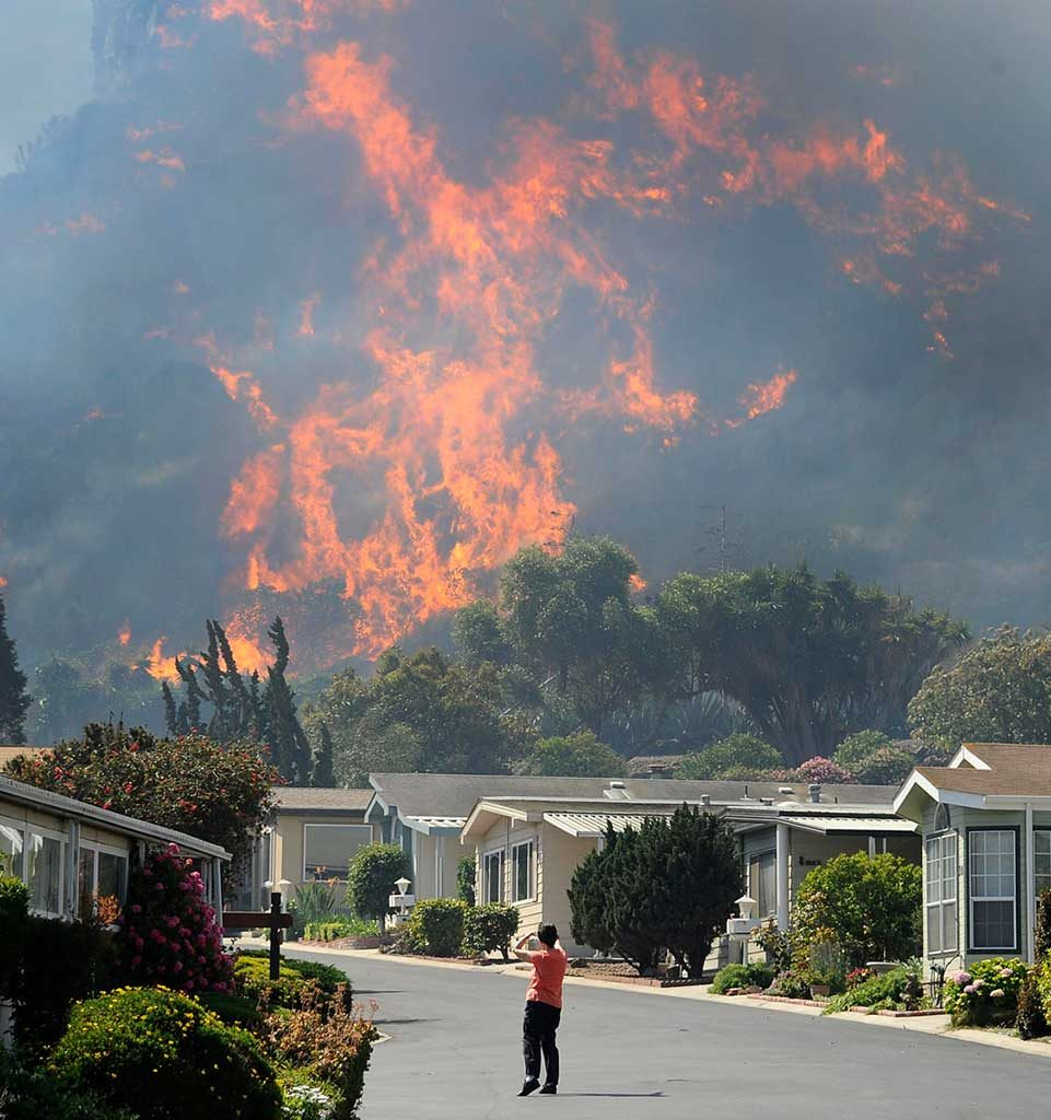 Homeowner watches as a wildfire bears down on their neighborhood.